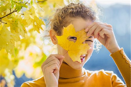 A woman looking through a hole in a leaf she's holding up to her face Stock Photo - Premium Royalty-Free, Code: 653-06534855