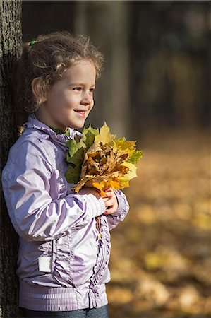 portrait looking away - A young cheerful girl holding a bunch of autumn leaves with pride Stock Photo - Premium Royalty-Free, Code: 653-06534877