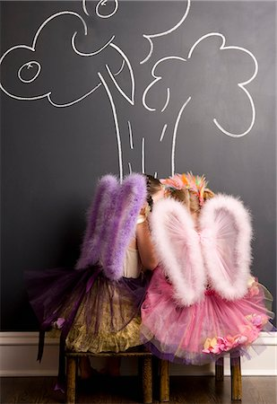Two girls dressed as angels in front of blackboard with image of tree Stock Photo - Premium Royalty-Free, Code: 653-06534905