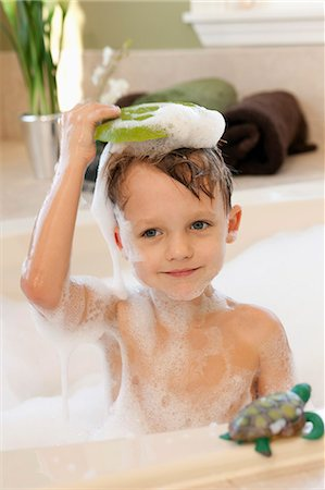 Boy holding bar of soap above head in bath Stock Photo - Premium Royalty-Free, Code: 653-06534914