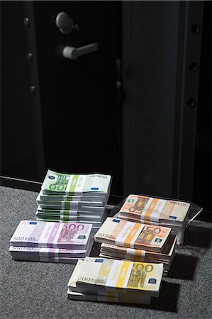 Stacks of large billed Euro banknotes on a table outside of a vault Stock Photo - Premium Royalty-Free, Code: 653-06534940