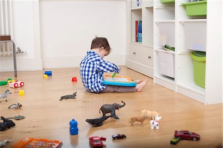 A boy sitting on the floor, drawing on a tablet, surrounded by various toys Stock Photo - Premium Royalty-Free, Code: 653-06534952
