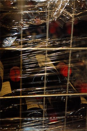 A metal crate filled with stacked red wine bottles and wrapped in plastic wrap Stock Photo - Premium Royalty-Free, Code: 653-06535052