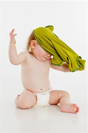 A baby girl pulling her shirt off Stock Photo - Premium Royalty-Free, Code: 653-06533661