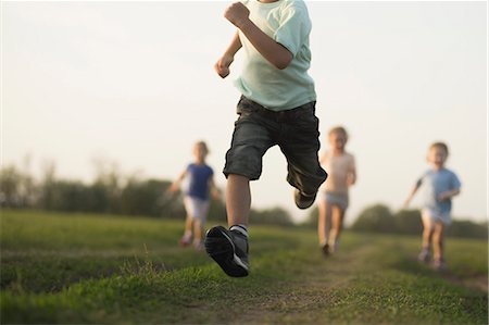 Low view of a boy running in a field with other children behind Stock Photo - Premium Royalty-Free, Code: 653-06533863