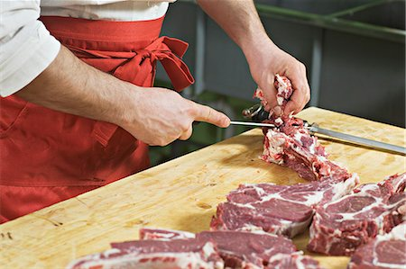 Detail of a man chopping meat Stock Photo - Premium Royalty-Free, Code: 653-06533882