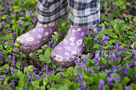 Low section of a girl standing in a garden with gumboots Stock Photo - Premium Royalty-Free, Code: 653-06533897