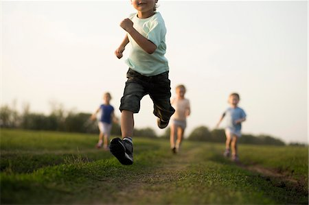 Low view of a boy running in a field with other children behind Stock Photo - Premium Royalty-Free, Code: 653-06533936