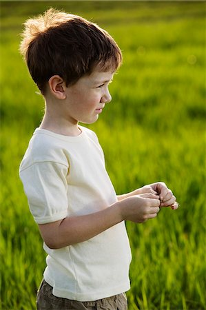 A young boy standing in a field Stock Photo - Premium Royalty-Free, Code: 653-06533949