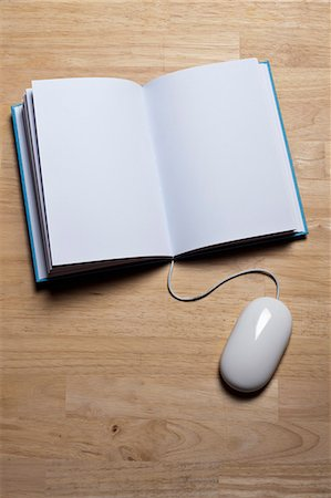 A hardcover book with a computer mouse attached to it Stock Photo - Premium Royalty-Free, Code: 653-06533953