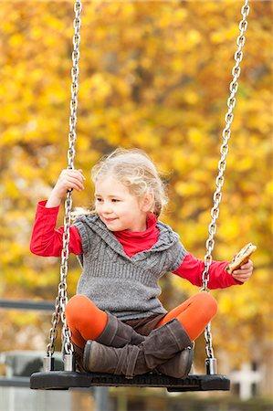 swing (sports) - Girl on swing holding sandwich Stock Photo - Premium Royalty-Free, Code: 653-06819599
