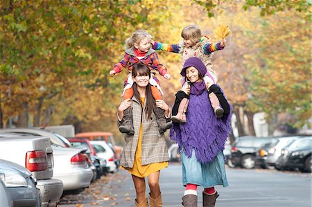 Two mothers with their daughters on their shoulders in Prenzlauer Berg, Berlin, Germany Stock Photo - Premium Royalty-Free, Code: 653-06819605