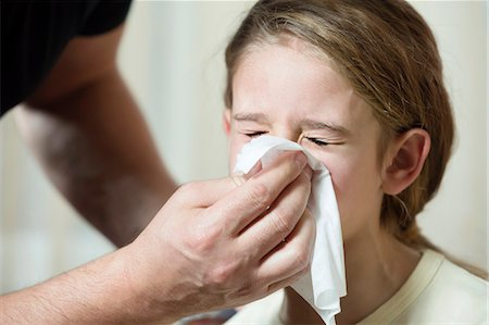 sad girls - Father wiping daughter's nose with tissue Stock Photo - Premium Royalty-Free, Code: 653-06819663