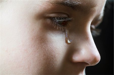 Close-up of a girl shedding a tear Stock Photo - Premium Royalty-Free, Code: 653-06819673