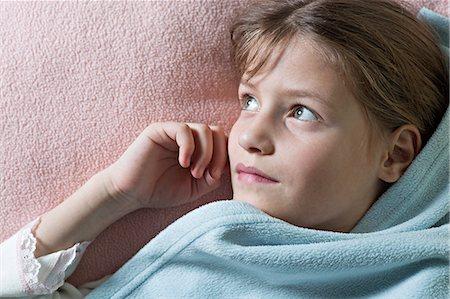 Daydreaming girl under blanket Stock Photo - Premium Royalty-Free, Code: 653-06819687