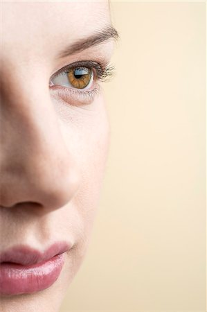 Close-up of beautiful brown eyed woman looking into distance Stock Photo - Premium Royalty-Free, Code: 653-06819692