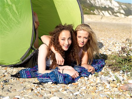 Two friends lying partially inside a beach tent on a rocky beach Stock Photo - Premium Royalty-Free, Code: 653-06819731