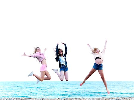 Three friends jumping in excitement on the beach Stock Photo - Premium Royalty-Free, Code: 653-06819732