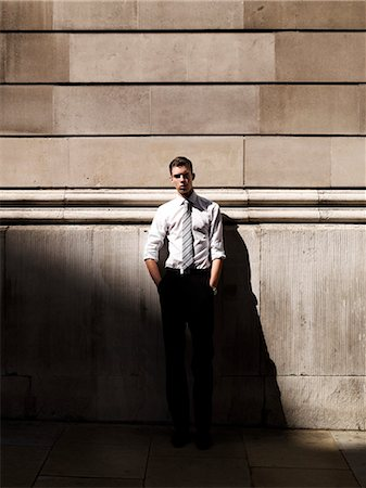 shadow - A young handsome businessman leaning against a building Stock Photo - Premium Royalty-Free, Code: 653-06819765