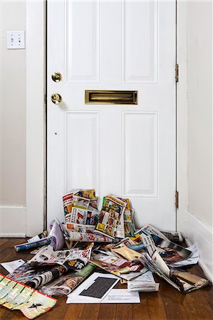 A heap of mail and newspapers under a mail slot in a home entrance hall Stock Photo - Premium Royalty-Free, Code: 653-06819783