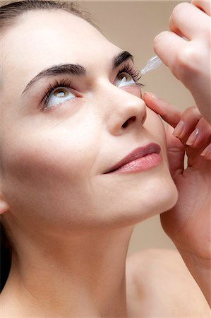 A serenely smiling young woman applying eye drops to her eyes Stock Photo - Premium Royalty-Free, Code: 653-06819846