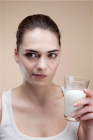 expresivo - A young woman making a face after taking a drink of milk Foto de stock - Sin royalties Premium, Código: 653-06819856