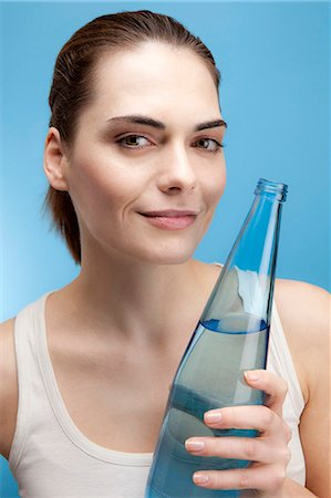 drinking water glass - A smiling young woman holding a glass bottle of water Stock Photo - Premium Royalty-Free, Code: 653-06819874