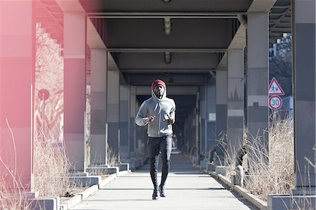 shadow - A hip young man jogging on a city sidewalk under a bridge Stock Photo - Premium Royalty-Free, Code: 653-06819915