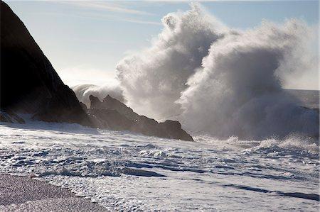 Sunlight shining on large waves crashing against rocks Stock Photo - Premium Royalty-Free, Code: 653-06819979