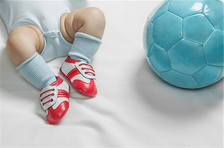 A baby boy wearing baby soccer shoes lying next to a soccer ball Stock Photo - Premium Royalty-Free, Code: 653-07234003