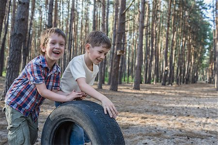 Two young boys pushing a tire in a wooded area Stock Photo - Premium Royalty-Free, Code: 653-07234015
