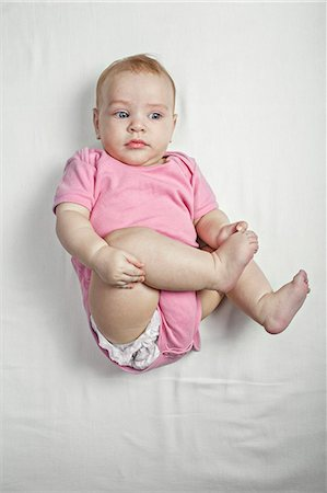 A baby girl lying on her back touching her barefoot curiously Stock Photo - Premium Royalty-Free, Code: 653-07234042