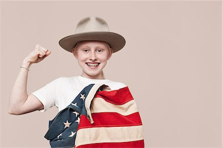 A smiling girl wearing a ranger hat wrapped in an American flag and making a fist Stock Photo - Premium Royalty-Free, Code: 653-07234061
