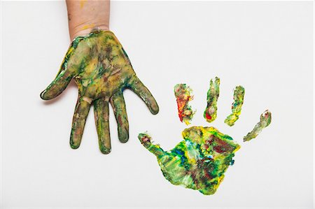 finger painting - Child with colorful painted hand beside her hand print on paper Stock Photo - Premium Royalty-Free, Code: 653-07233738