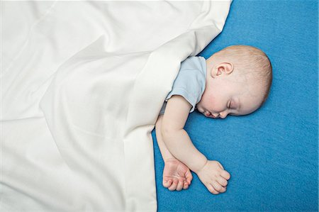 Sleeping baby on bed under blanket Stock Photo - Premium Royalty-Free, Code: 653-07233768