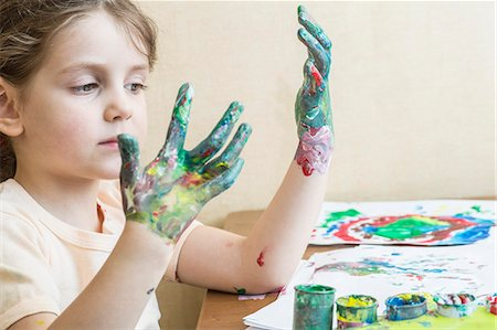 finger painting - Girl looking at her painted hands Stock Photo - Premium Royalty-Free, Code: 653-07233760