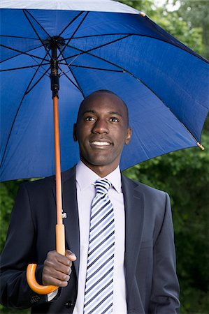 people with umbrellas in the rain - Happy businessman holding umbrella Stock Photo - Premium Royalty-Free, Code: 653-07233885