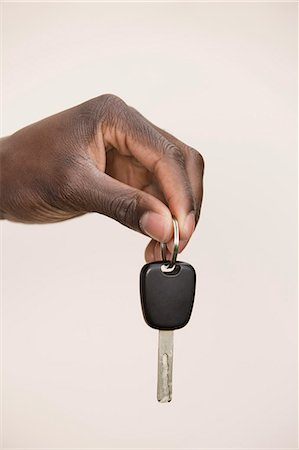 finger holding a key - Studio shot of man holding car key Stock Photo - Premium Royalty-Free, Code: 653-07233887