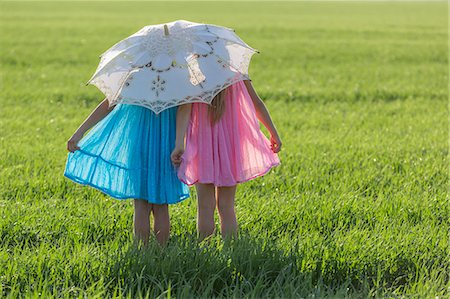 Twin sisters standing in a sunny field under an umbrella Stock Photo - Premium Royalty-Free, Code: 653-07233988