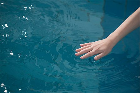 female hand - A young girl's hand rippling the water in a swimming pool Stock Photo - Premium Royalty-Free, Code: 653-07233996