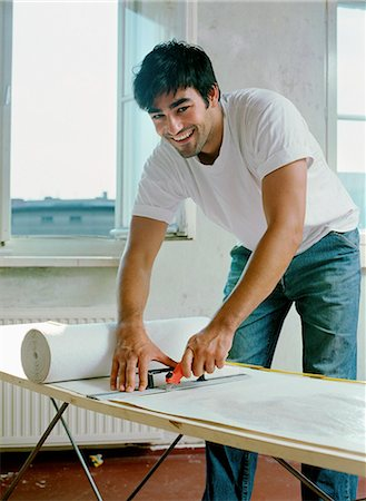 A man cutting paper with work tool, portrait Stock Photo - Premium Royalty-Free, Code: 653-07539045