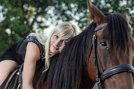 Young woman lying on horse Stock Photo - Premium Royalty-Free, Code: 653-07539108