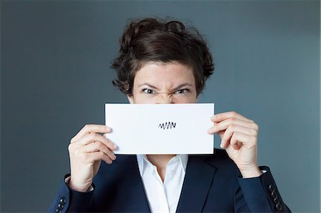 Portrait of mid adult woman holding paper with zigzag sign, close-up Stock Photo - Premium Royalty-Free, Code: 653-07539123