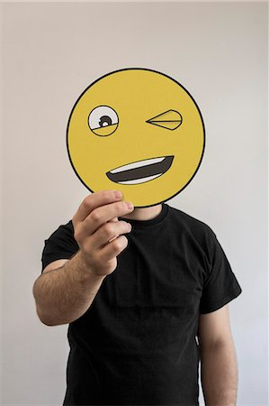 Man holding winking emoticon face in front of his face Stock Photo - Premium Royalty-Free, Code: 653-07708039