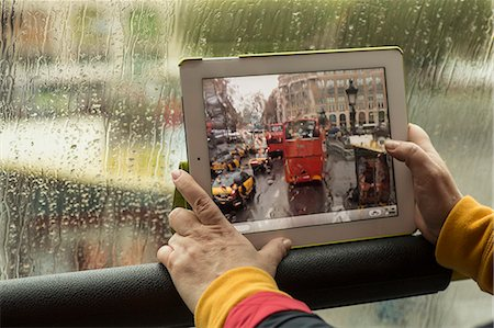 Cropped image of woman photographing bus with digital tablet Stock Photo - Premium Royalty-Free, Code: 653-07708030