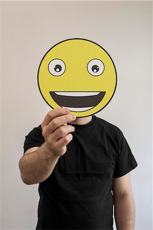 person holding sign - Man holding a really happy emoticon face in front of his face Stock Photo - Premium Royalty-Free, Code: 653-07708048