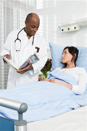 doctor and patient - A doctor talking to a patient lying in a hospital bed Stock Photo - Premium Royalty-Free, Code: 653-07761285