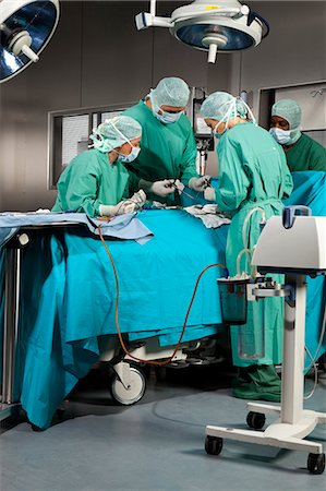 Doctors and nurses operating on a patient in a operating room Stock Photo - Premium Royalty-Free, Code: 653-07761287