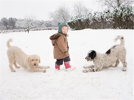 Baby girl with Portuguese Water Dogs in snow Stock Photo - Premium Royalty-Free, Code: 653-07761359