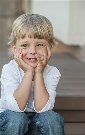 picture - Cute boy sitting with head in hands at porch Stock Photo - Premium Royalty-Free, Code: 653-07761449